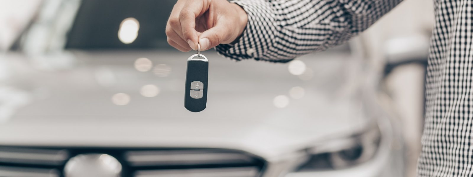 Cropped shot of a man holding car key, standing in front of a new automobile at the dealership. Male driver posing with car keys in his hand, copy space. Rental service, automotive retail concept