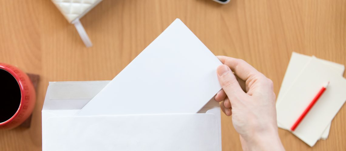 Female hands holding an envelope with a blank paper sheet over the office desk. Top view with copy space