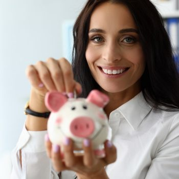 Portrait of beautiful brunette putting saved coin in thrift-box. Wonderful businesslady looking at camera with gladness and smiling. Piggy bank concept