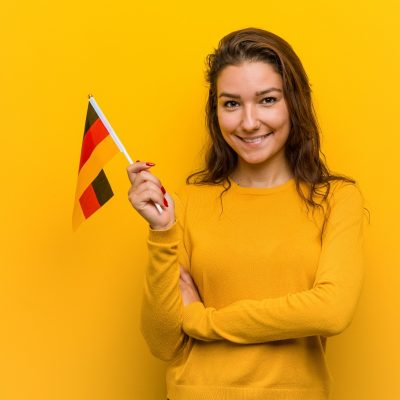 Young european woman holding a germany flag smiling confident with crossed arms.