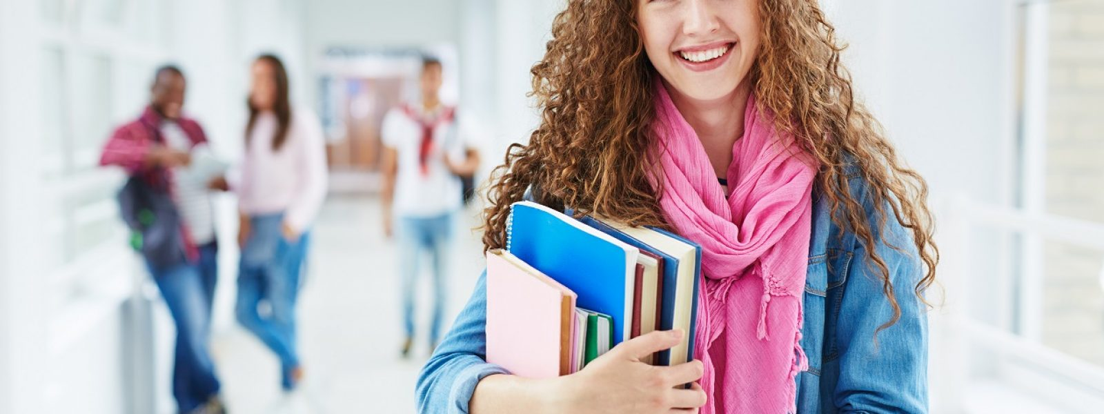 Smiling teenage girl with books looking at camera