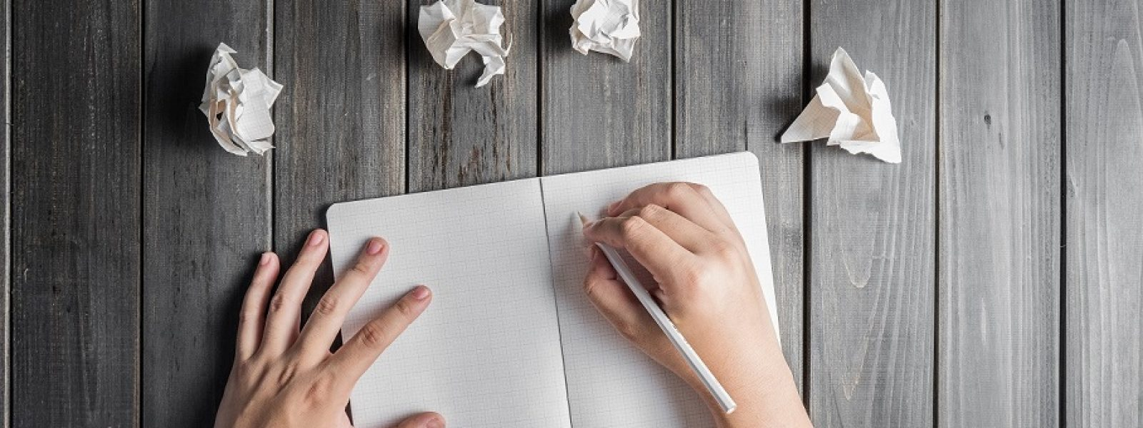 hands wresting the sheet of paper and making paper ball after mistake during writing top view